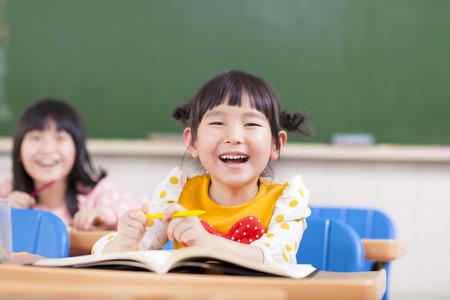ni�os estudiando: felices los ni�os que estudian en un aula Foto de archivo