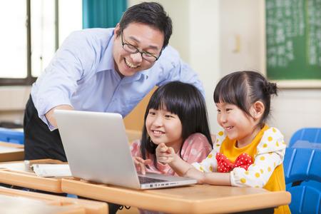 maestra ense�ando: Ense�ar a los ni�os del profesor con un ordenador port�til Foto de archivo