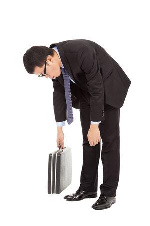 sehr müde Geschäftsmann bücken und halten Aktenkoffer