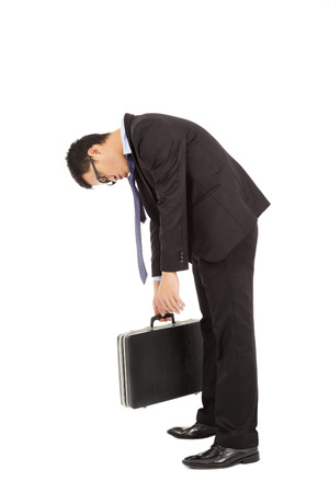 negativity: exhausted businessman stoop and holding briefcase Stock Photo