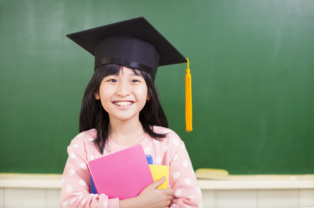 smiling girl wear a graduation hat and holding books photo