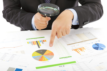 business tool: businessman hold a magnifying glass to explore