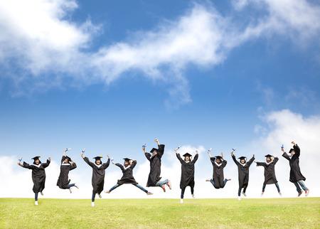 Studenten vieren afstuderen en gelukkige sprong Stockfoto