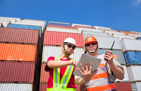 two workers with tablet  and standing before stack of containers photo