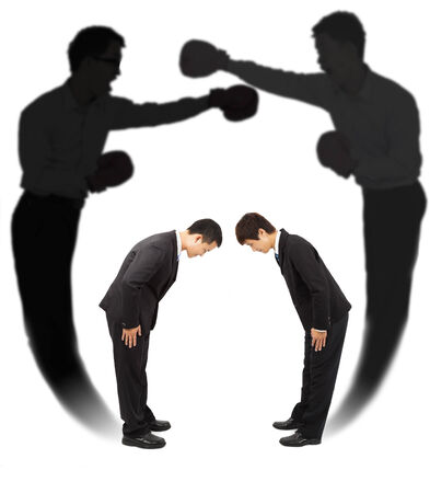 Two businessman bow each other with fighting shadow photo