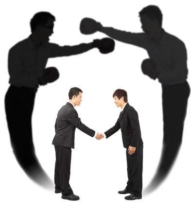Two businessman handshake with fighting shadow photo