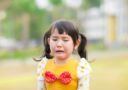 crying: crying little girl in the park