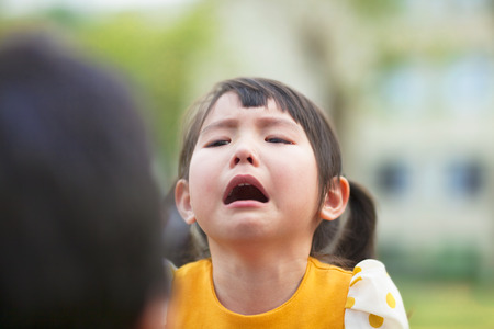 Children cry: little asian girl crying and look at her parents