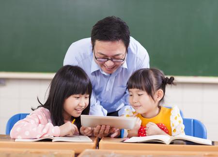maestra ense�ando: Ense�ar a los ni�os del profesor con tableta digital Foto de archivo