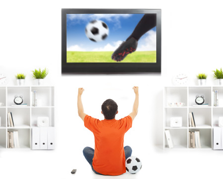 kick around: happy fan watching soccer game and raised hands Stock Photo