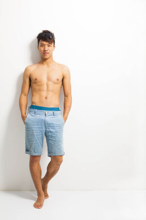 sexy young man standing and depend on wall