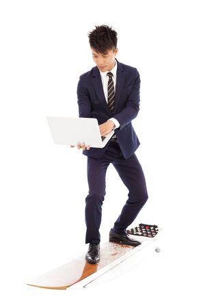 businessman using a laptop on a  surfboard  photo