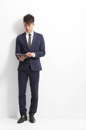 businessman using tablet and standing front of wall photo