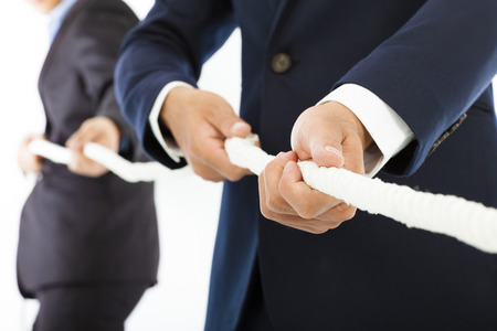 Two businessman work together and playing tug of war photo