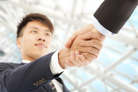business agreement: Two businessman shaking hands greeting each other