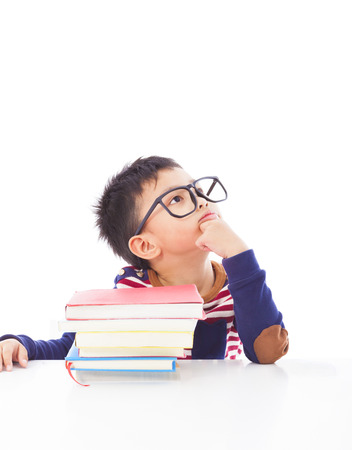 little boy thinking or dreaming during preparing homework photo