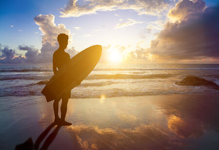 surfboard fin: surfing man standing on a beach with sunset
