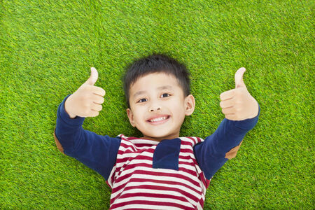 happy kid lying and thumb up  on a meadow Stock Photo
