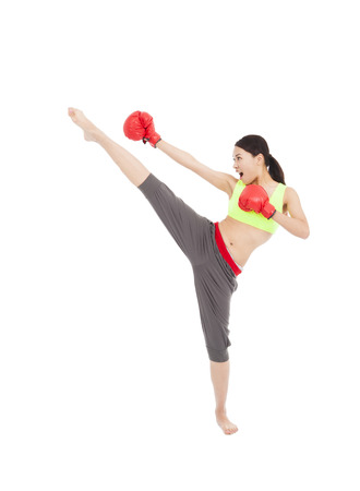 kick boxing: pretty female boxer  is kicking and fisting Stock Photo