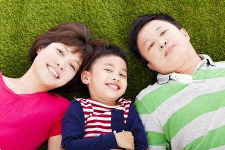 happy parents and son lying on a meadow photo