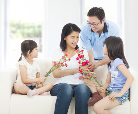 Daughters and father handing mother carnations  photo