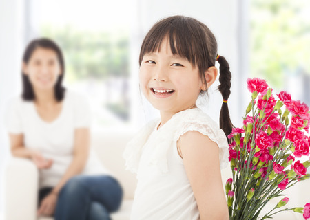 cute girl looking back and hiding a bouquet of carnations photo
