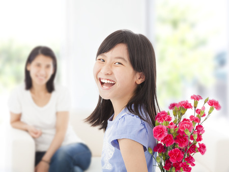 happy girl looking back and hiding a bouquet of carnations Stock Photo