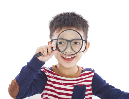 adorable boy holding a magnifier and watching through photo