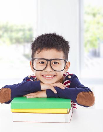 prone: smiling little boy lying on books