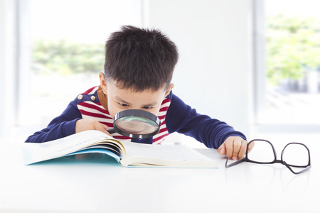 little boy detective searching clues from books Stock Photo