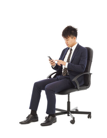 man in chair: young businessman touching smart phone on chair