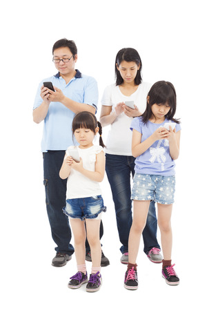 Asian Family standing and using smart phone together photo