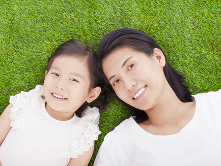 smiling mother and daughter lying on a meadow photo
