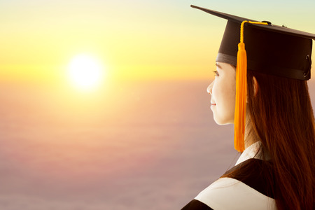 pretty female graduation is thinking future with sunset background photo