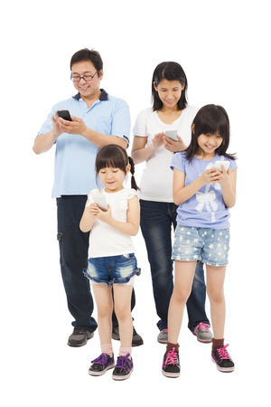 tableta: Šťastná rodina stojí a pomocí inteligentního telefonu spolu