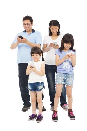 Glückliche Familie stehen und zusammen mit Smartphone Standard-Bild
