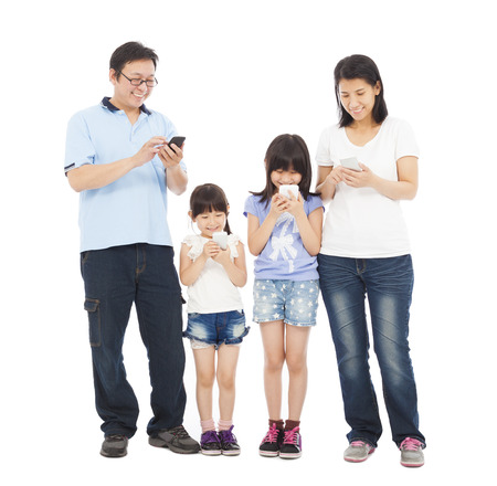 Family standing a row and using smart phone together photo