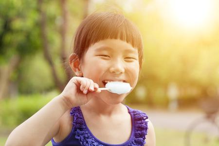 Счастливый маленькая девочка, едят мороженое с фоне заката
