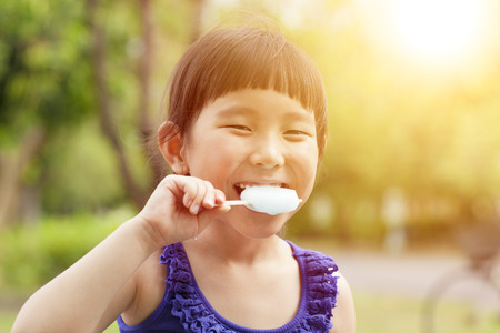 happy little girl eating ice cream with sunset background photo