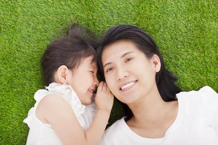 padres hablando con hijos: madre e hija susurrando chismes sobre la hierba