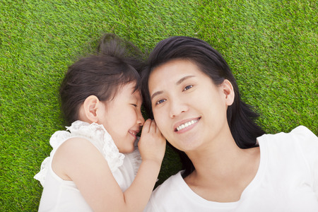 daughter: mother and daughter whispering gossip on the grass Stock Photo
