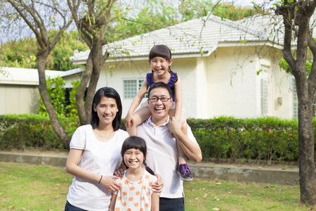 彼らの家の前に幸せな家族の立っています。
