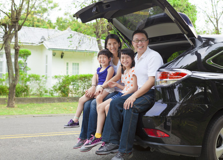 casita de dulces: familia feliz sentado en el coche y su casa detrás de Foto de archivo