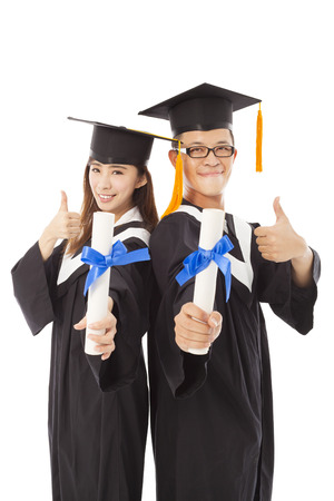 college graduation: happy graduating students with thumb up Stock Photo