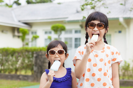 Cute little Girls  Eating Ice Cream before their house Stock Photo