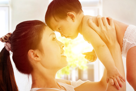 Happy  mother holding adorable child baby with sunrise background photo