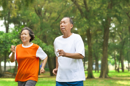 happy senior couple running together in the park photo