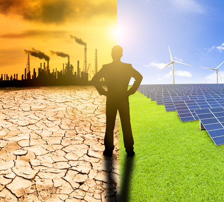 pollution and clean energy concept. businessman watching windmills solar panels and refinery with air pollution photo