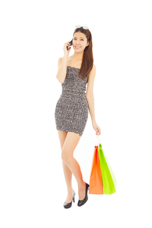 young  woman holding shopping bags and talking on the phone photo
