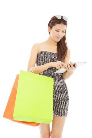 young  woman holding shopping bags and using  the tablet photo